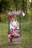Kissing Booth. Adorable little girl sitting in a kissing booth and looking at her jar of nickels stock photo