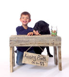 Kissing Booth - Open For Business. A little boy giggles his way through getting a kiss at the doggy kissing booth stock photo