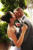 Kissing bride and groom with glasses Royalty Free Stock Photos