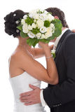 Kissing bride and groom hidden behind bride Bouquet isolated on Royalty Free Stock Photography
