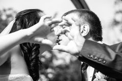 Kissing bride and groom holding hands in shape of heart Stock Image