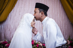 Kissing the bride. Groom kissing bride's forehead after solemnization ceremony Stock Photos