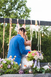 Kissing Bride and Groom at Table. With flowers Royalty Free Stock Photo