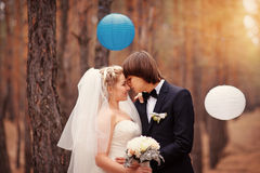 Kissing bride and groom in their wedding day near autumn tree in Royalty Free Stock Photo