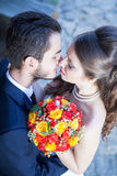 Kissing bride and groom from up shooting Stock Photography