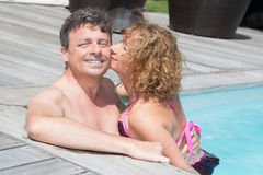 Kissing and charming couple having fun in swimming-pool Stock Image