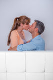 Kissing couch couple in hotel. Kissing couple relaxing in new home stock photo