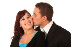 Kissing Couple. Hansome man kissing his beautiful smiling girlfriend's cheek Royalty Free Stock Photo