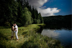Kissing couple. Couple kissing in the grass by the lake Royalty Free Stock Photos