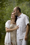 Kissing couple. Young couple smiling looking forward Royalty Free Stock Photography
