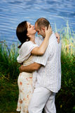 Kissing couple. Young couple flirting and kissing by the lake Stock Photography