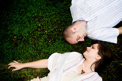 Kissing couple. Young couple laying in the grass looking at each other Royalty Free Stock Photography