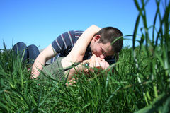 Kissing couple. Young couple kissing on a grass Royalty Free Stock Image