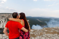 Kissing couple against beautiful mountains Stock Images