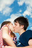 Kissing couple on a background of the blue sky royalty free stock image