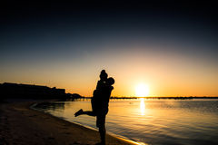 Kissing Couple with Beach Sunset. A couple happily in love kissing before a beautiful sunset on the beach Royalty Free Stock Photos