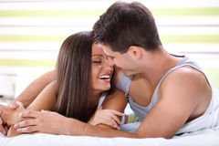 Kissing couple in bed. Love couple lying in bed kissing and looking each other Royalty Free Stock Image