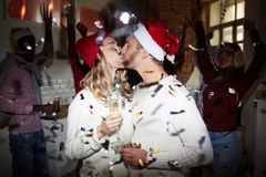 Xmas kiss. Kissing couple with champagne on background of dancing friends enjoying xmas party stock photo