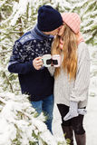 Kissing couple with drinks in cups in forest among fir trees Royalty Free Stock Images