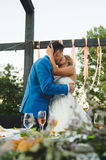 Kissing Couple at Festive Table. Couple kissing at festive table at yard Royalty Free Stock Photography