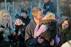 Kissing couple on a flashmob of soap bubbles in Volgograd. Volgograd, Russia - April 01, 2011: Kissing couple on a flashmob of soap bubbles in Volgograd Royalty Free Stock Images