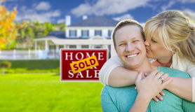 Kissing Couple In Front Sold Real Estate Sign and House Stock Photography