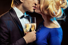 Kissing couple holding glases of a champagne Stock Images