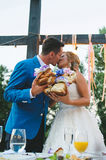 Kissing Couple Holding Loaf. Kissing couple holding parts of loaf with flowers Royalty Free Stock Photos