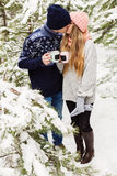 Kissing couple with hot drinks in forest among fir trees Stock Photography