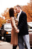 Kissing couple outdoors. Kissing  couple mature and looking at the camera on a chilly day in the fall. she's in a dress and he's wearing a sports jacket Stock Image