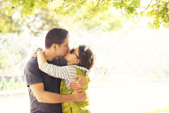 Kissing couple in the park stock photography