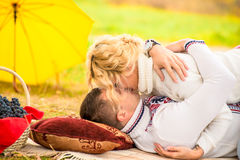 Kissing couple on the plaid in park Royalty Free Stock Images