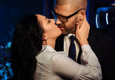 Kissing couple. Portrait of a sensual brunette and handsome businessman. Office romance concept Stock Photography