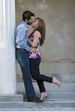 Kissing Couple Posing. A young couple kissing during an embrace Royalty Free Stock Photography
