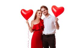 Kissing couple posing on white background with balloons heart. stock photography