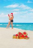 Kissing couple in santa hats at sea beach Royalty Free Stock Image