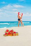 Kissing couple in santa hats at sea beach Stock Images