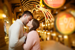 Kissing couple in shopping mall. Amid garlands Royalty Free Stock Images