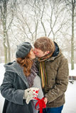 Kissing Couple While Snowing. Young pair kissing outdoors, it is winter and snowing, woman is pregnant, she is holding a cup with painted hearts royalty free stock photos