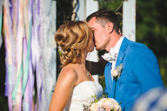 Kissing Couple in Sunlight. Kissing couple at wedding ceremony in sunlight Stock Image