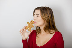 Kissing a gingerbread cookie Royalty Free Stock Image