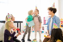 Kissing girl for gift at childrens birthday party royalty free stock images