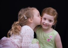 Kissing girls. Little girl kissing her big sister Royalty Free Stock Photos