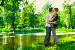 He is kissing her passionately. Teenagers: man are kissing girlfriend on nature near a lake. Full-length portrait Royalty Free Stock Photos