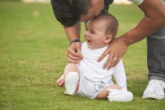 Kissing little son. Father bending to kiss his adorable baby boy on forehead royalty free stock photos