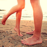 Kissing lovers - couple on beach love concept. Showing feet in close up. Woman standing on toes to kiss men at sunset during romantic summer holidays vacation royalty free stock photography