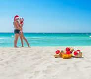 Kissing lovers couple in santa hats at sea beach Royalty Free Stock Image