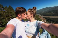 Kissing man and woman on top mountain Stock Photo
