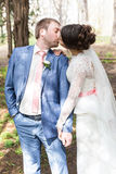 Kissing married couple on sunny alley among trees Royalty Free Stock Photos