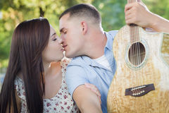 Kissing Mixed Race Couple Portrait with Guitar in Park Stock Image